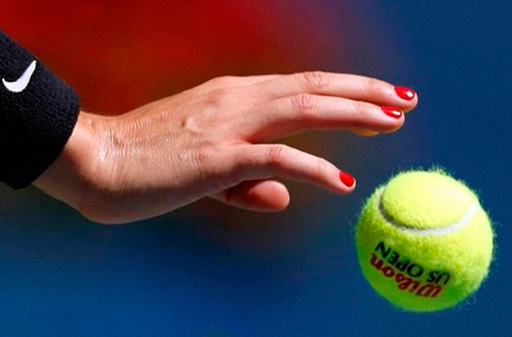 The hand tosses the tennis ball